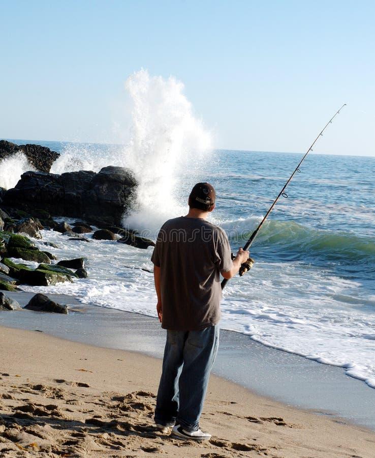 Pesca do homem e onda whaching foto de stock royalty free