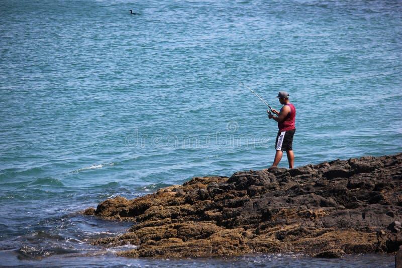 Pesca do homem nas pedras do mar imagens de stock royalty free