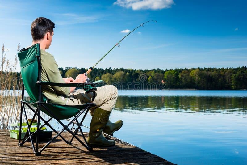 Pesca do homem no lago que senta-se no molhe fotos de stock