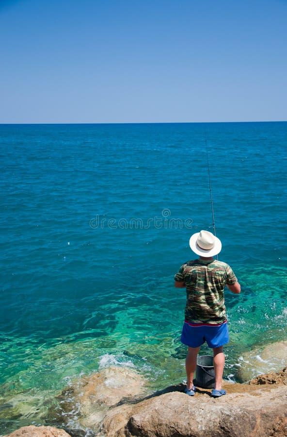 Pesca do homem no mar imagens de stock royalty free