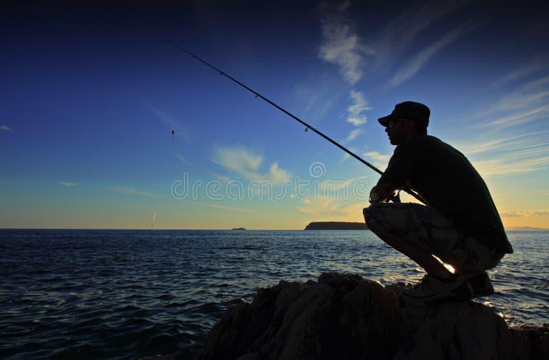 Pesca do homem no por do sol imagens de stock royalty free