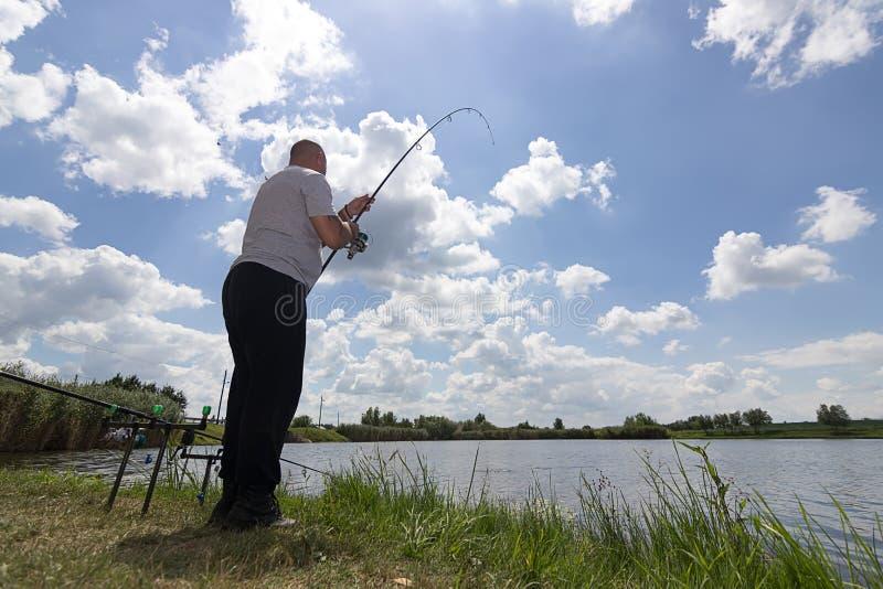 Pesca do homem novo, pescador que guarda a haste na ação, pescador que guarda a haste na ação foto de stock royalty free