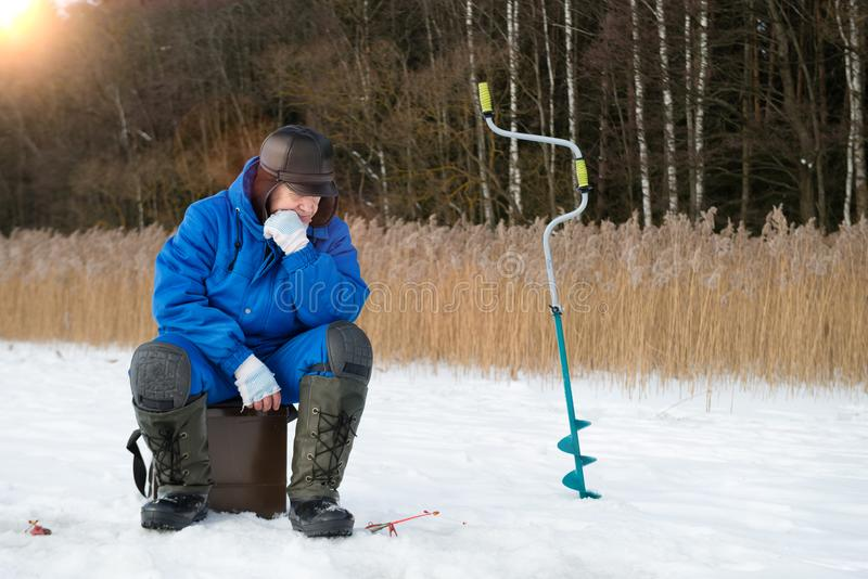 Pesca do inverno A captura de espera do homem no dia do frio do inverno fotos de stock royalty free