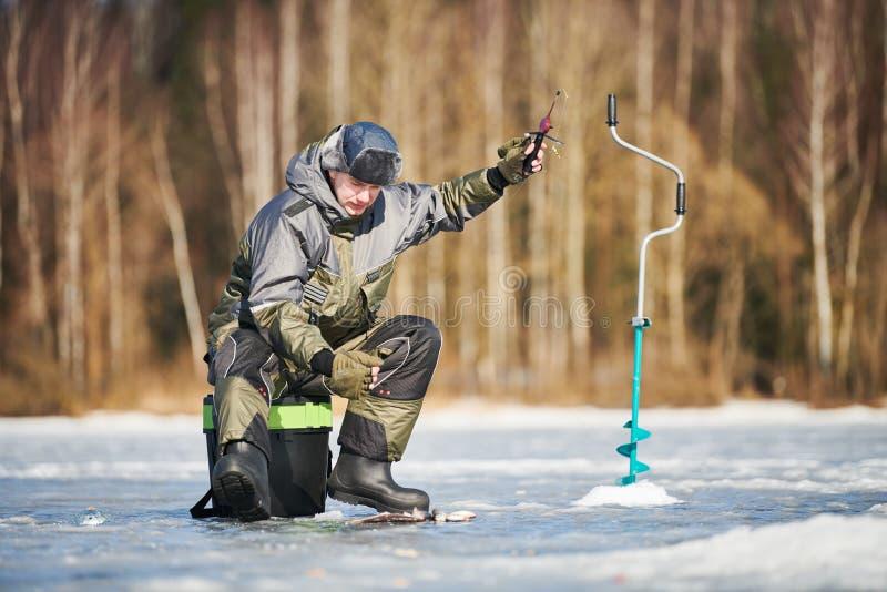 Pesca do inverno no gelo pescador ou pescador que engancham os peixes imagens de stock