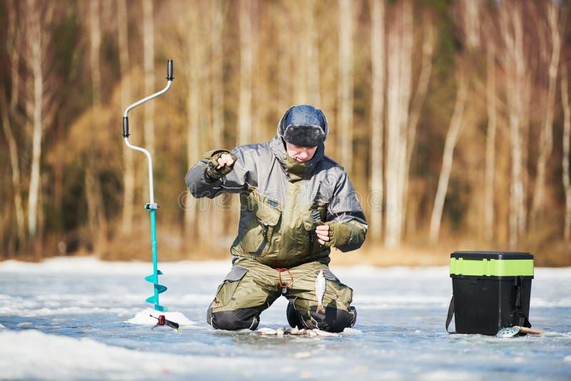 Pesca do inverno no gelo pescador ou pescador que engancham os peixes foto de stock royalty free