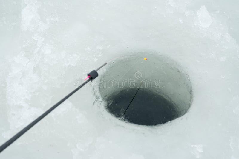 Pesca do inverno Vara de pesca do inverno ao lado do furo no gelo fotos de stock royalty free