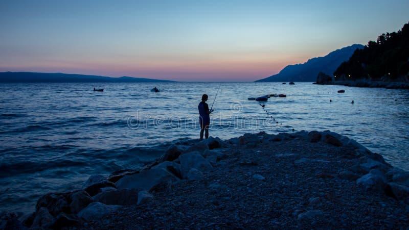 Pesca do litoral do por do sol fotos de stock royalty free
