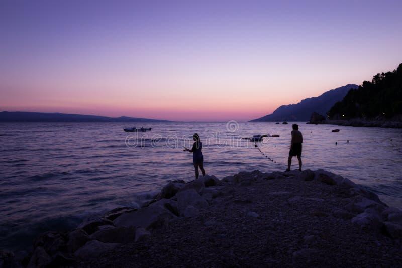 Pesca do litoral do por do sol fotografia de stock