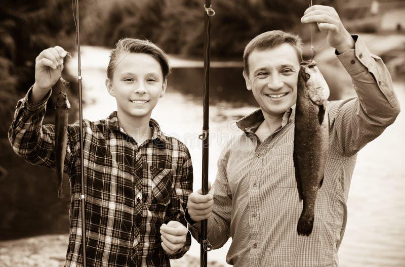 Pesca do menino e do homem imagens de stock royalty free