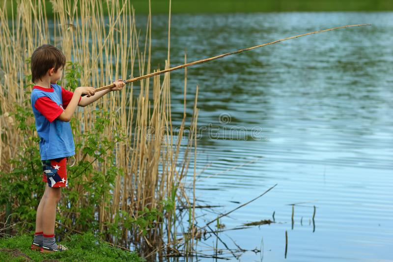 Pesca do menino no lago com uma haste fotos de stock