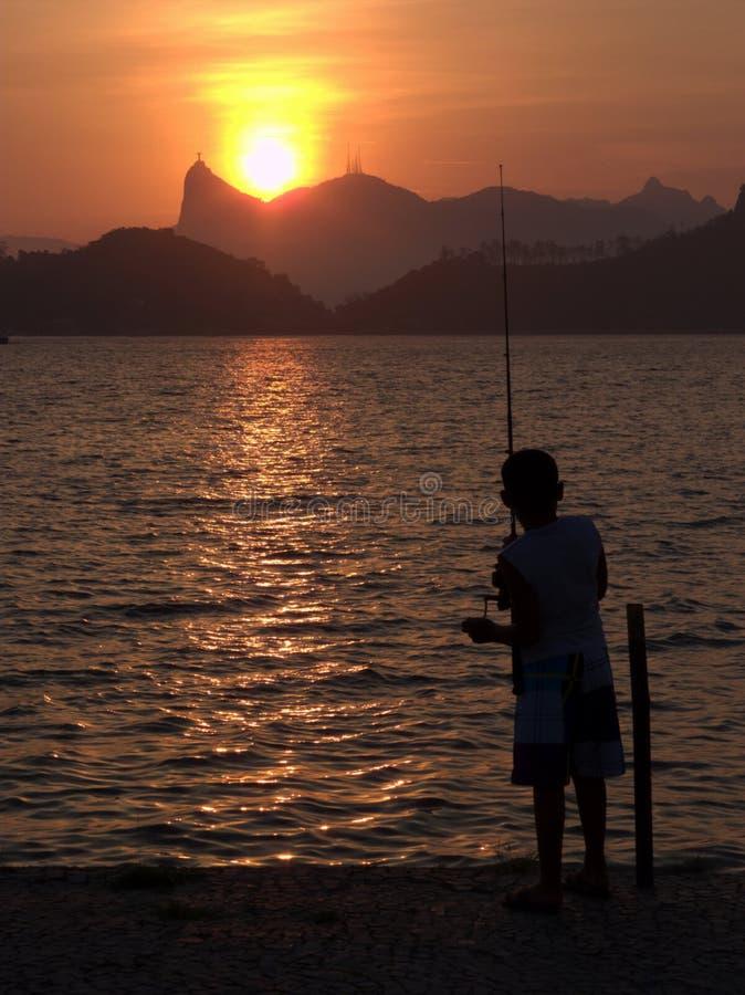 Pesca do miúdo no por do sol em Rio de Janeiro foto de stock royalty free