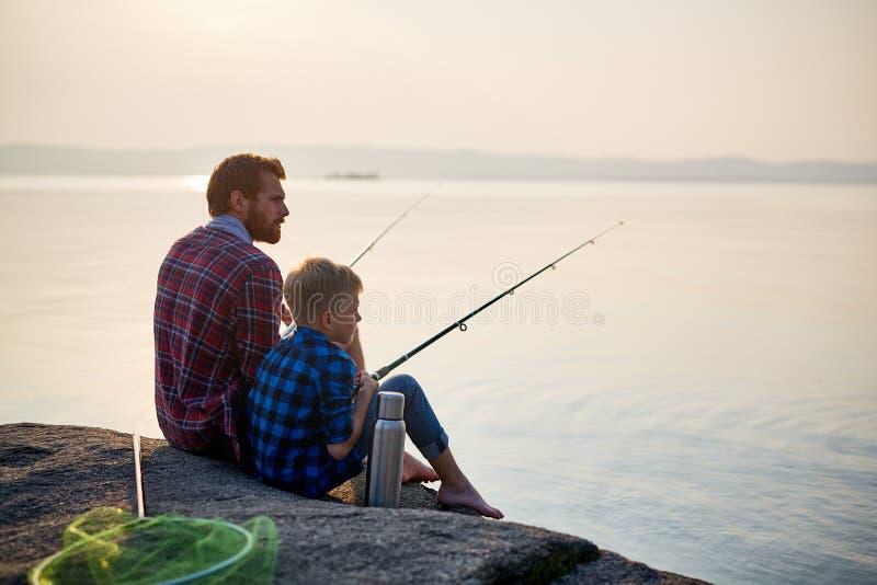 Pesca do pai e do filho no por do sol imagens de stock