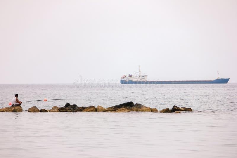A pesca do pescador com hastes de giro, carretéis no lago molha fotos de stock royalty free
