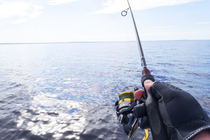 Pesca en el lago Manos del pescador con la ca?a de pescar Tiro macro La ca?a de pescar y las manos del pescador sobre el lago rie foto de archivo