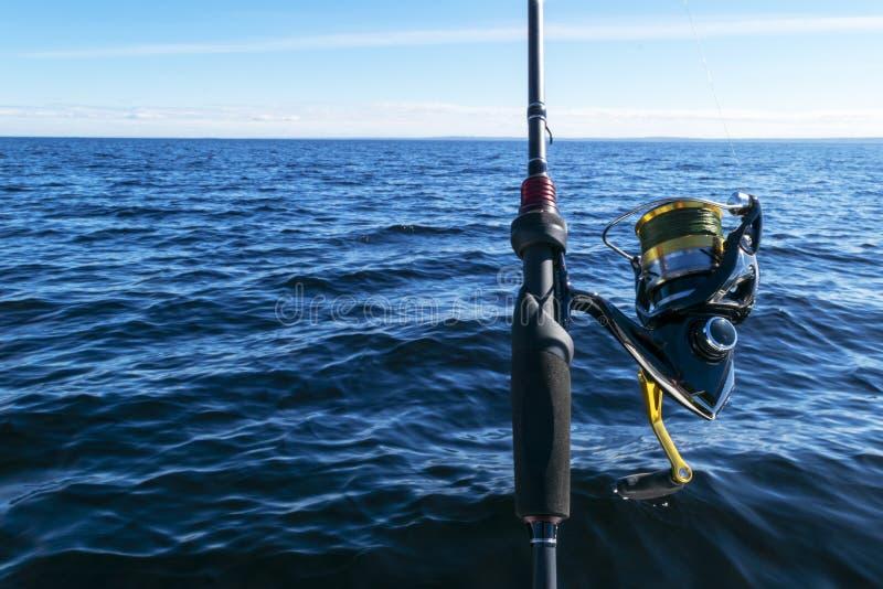 Pesca en el lago Manos del pescador con la ca?a de pescar Tiro macro La ca?a de pescar y las manos del pescador sobre el lago rie imágenes de archivo libres de regalías