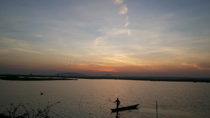 pesca en el medio del lago en la oscuridad imagen de archivo