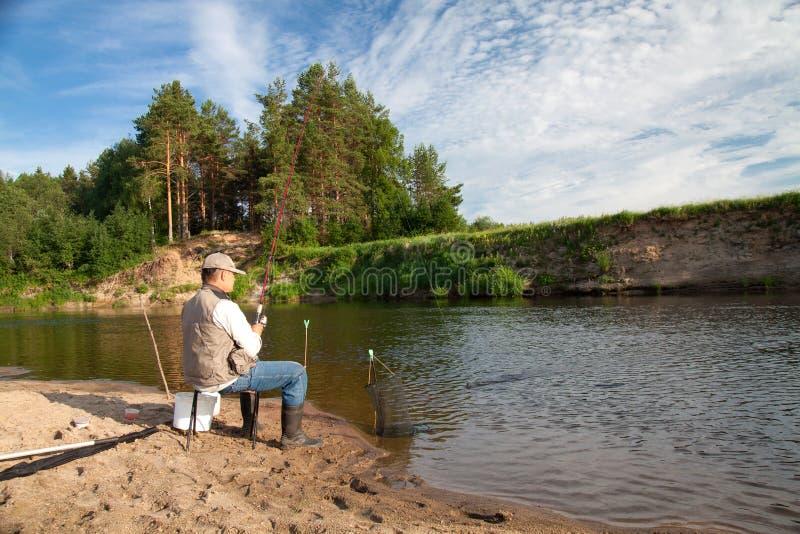 Pesca en el río en un lugar rural en un día de verano imagenes de archivo