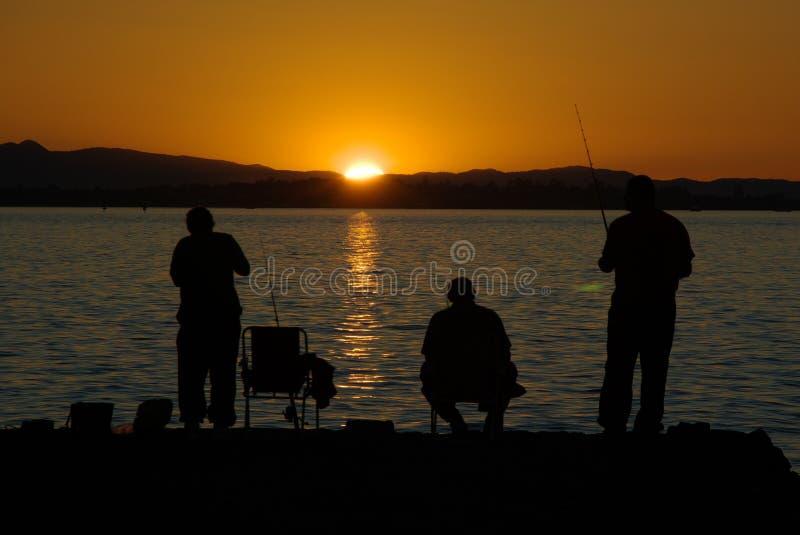 Pesca en la puesta del sol foto de archivo