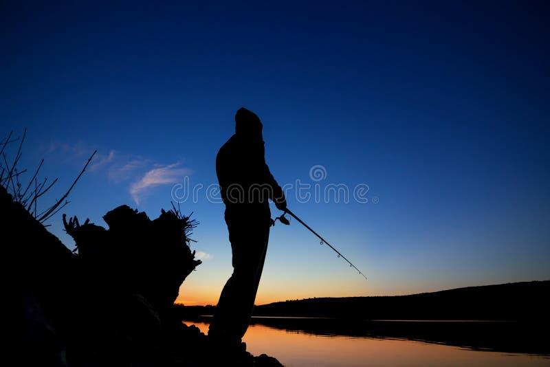 Pesca en la puesta del sol cerca del mar imagen de archivo libre de regalías