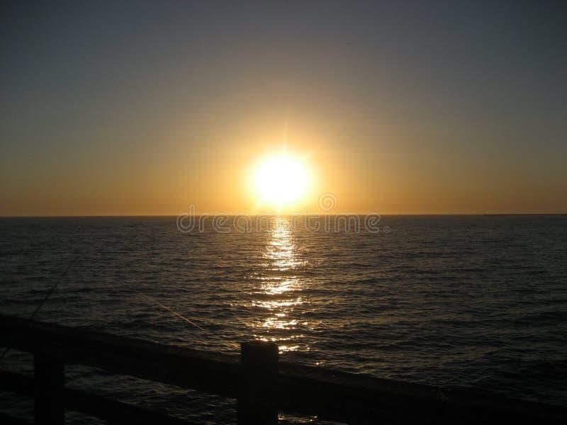 Pesca en la puesta del sol en el embarcadero de la costa fotografía de archivo libre de regalías