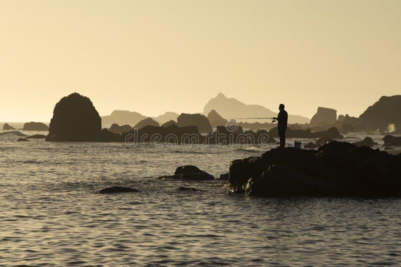 Pesca en mar de la puesta del sol imagen de archivo
