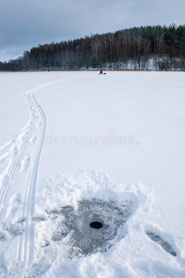 Pesca en un lago congelado en invierno foto de archivo libre de regalías