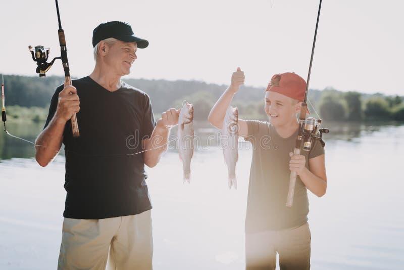Pesca feliz del abuelo y del nieto en el río fotografía de archivo libre de regalías