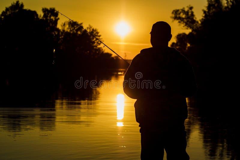 pesca giro no por do sol Silhueta de um pescador imagens de stock royalty free
