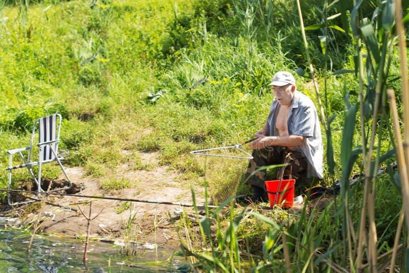 Pesca idosa do homem no lado de um lago fotografia de stock royalty free