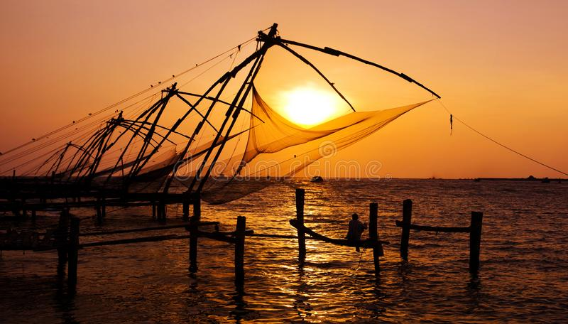 Pesca india del hombre bajo grandes redes chinas en Cochin, Kerela, la India imagen de archivo
