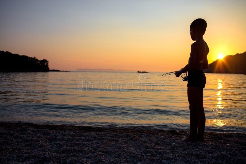 Pesca joven del muchacho en la costa imagen de archivo libre de regalías
