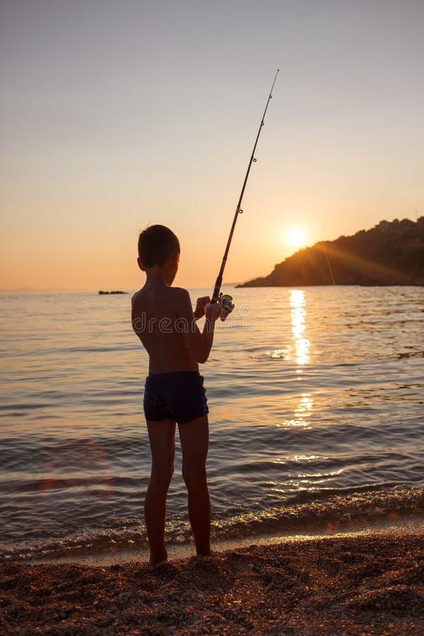 Pesca joven del muchacho en la costa foto de archivo