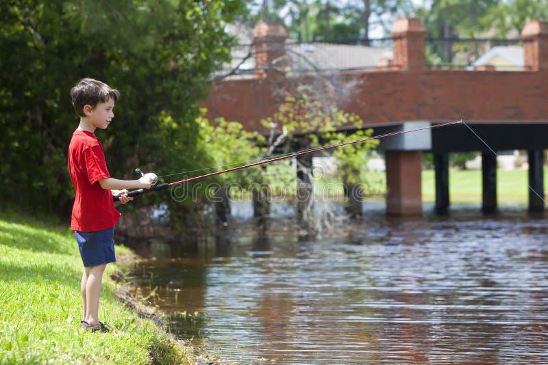 Pesca joven del muchacho en un río foto de archivo libre de regalías