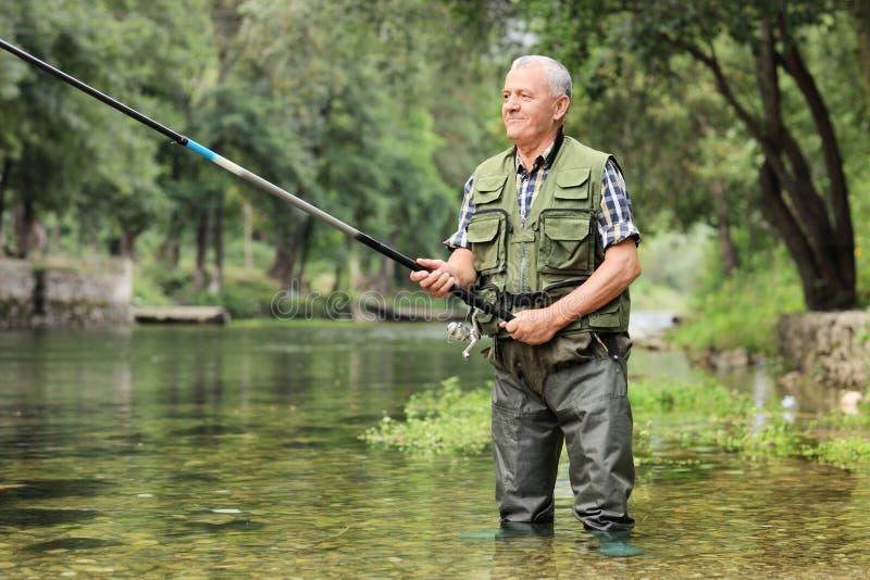 Pesca madura alegre del pescador en un río foto de archivo libre de regalías