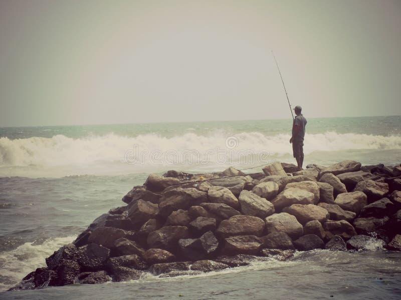 A pesca morna ensolarada das rochas solitárias das ondas do mar do pescador acena a pesca foto de stock royalty free