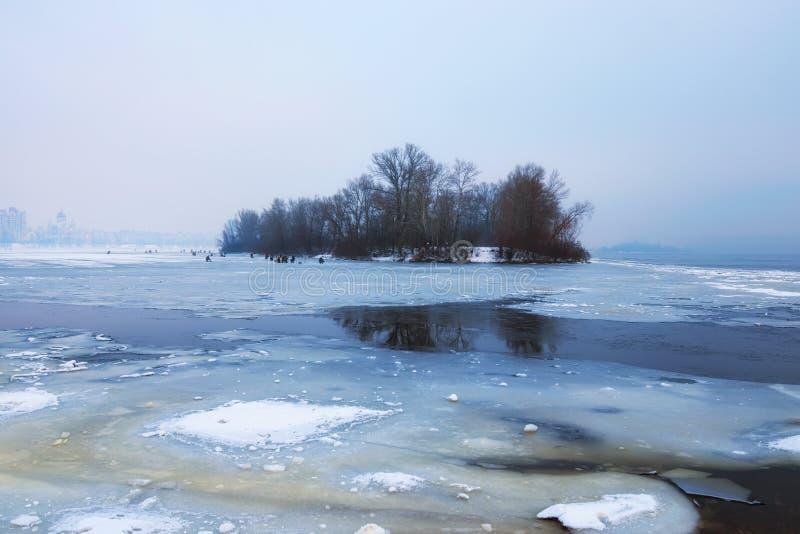 Pesca peligrosa del afición-invierno El río de Dnipro fue cubierto con el primer hielo fino pero los amantes de la pesca del invi imagenes de archivo