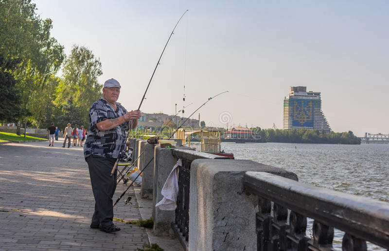Pesca senior del pescatore su un argine del fiume di Dnepr fotografia stock libera da diritti