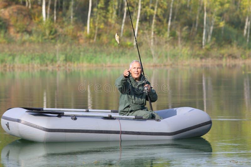 Pesca senior sul lago da una piccola barca fotografie stock