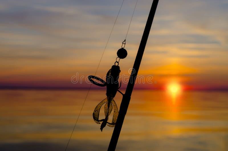 Pesca Silueta de trastos en fondo de la puesta del sol imagen de archivo