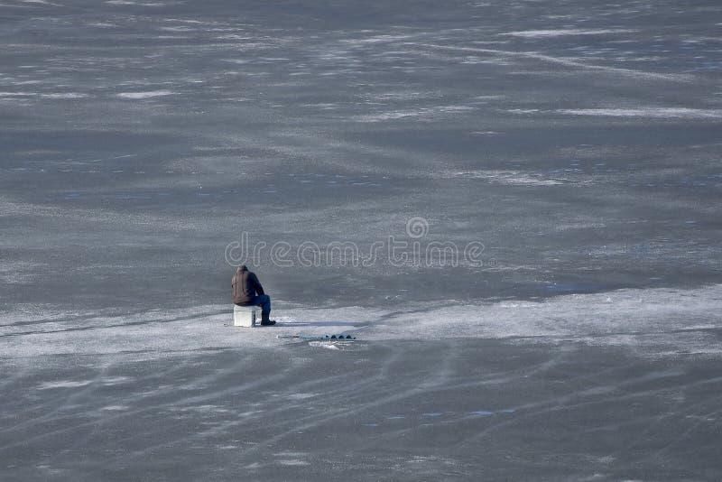 Pesca sul ghiaccio sul fiume Pescatore sul lago congelato fotografie stock libere da diritti