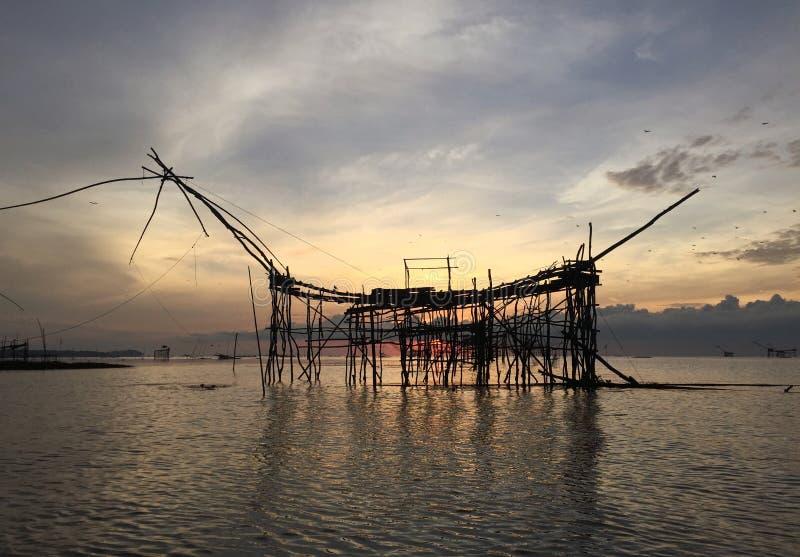 Pesca tradicional de la vieja cultura en el lago por la red de inmersión cuadrada de madera en la salida del sol del tiempo de ma imagenes de archivo