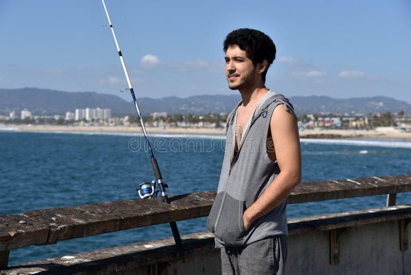 Pesca turistica maschio contenta sul pilastro fotografie stock