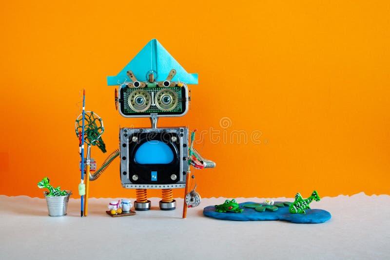 Pesca y vacaciones Robótica. Robot angler con vara de pesca captura peces en un estanque. lago azul, lirio de agua contra naranja imagen de archivo