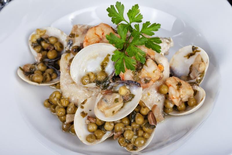 Pescadas no molho e nos camarões dos moluscos com ervilhas imagens de stock royalty free