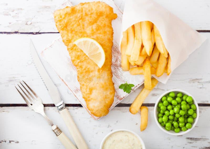 Pescado frito con patatas fritas brit?nicos tradicionales con la salsa de t?rtaro en la tajadera con la bifurcaci?n y cuchillo y  imagenes de archivo