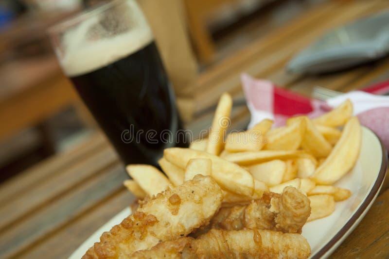 Pescado frito con patatas fritas con la cerveza oscura fotos de archivo