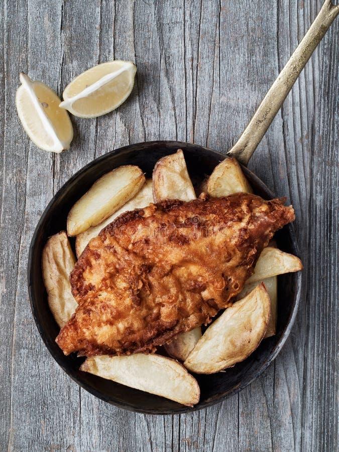Pescado frito con patatas fritas ingleses tradicionales rústicos imagen de archivo libre de regalías