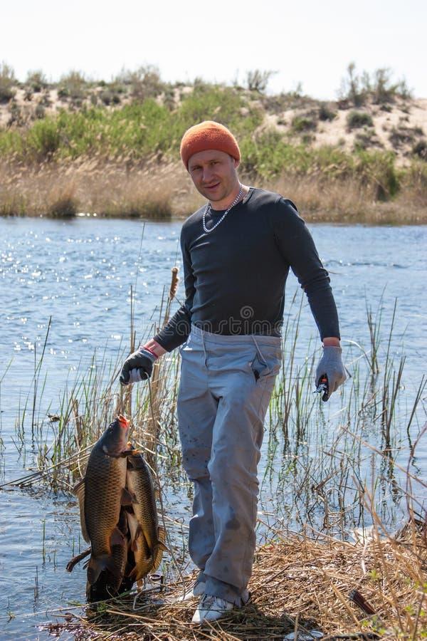 Pescador afortunado feliz que guardara uma carpa grande no rive imagens de stock royalty free