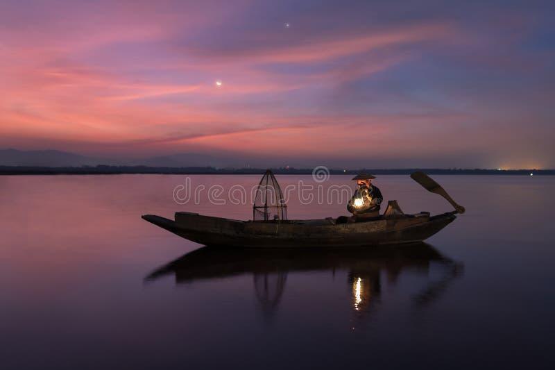 Pescador asiático no barco de madeira que procura peixes de água doce imagens de stock