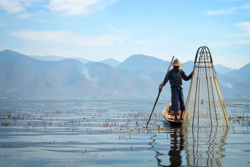 Pescador birmano en pescados de cogida del barco de bambú de la manera tradicional con la red hecha a mano Lago Inle, Myanmar Bir fotos de archivo